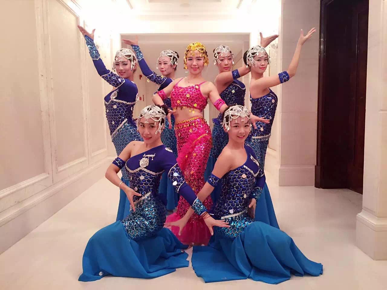 舞蹈《年年有余》的服装也是非常夺目和漂亮的,赵丽萍身着玫红色美人鱼裙,以金色鳞片为装饰,其他演员身着蓝色美人鱼裙以银色鳞片为装饰,在蓝色的海洋背景中,加上色彩斑斓的灯光变幻,演员们随歌而舞、扭动腰肢,呈现出一派鱼跃欢腾、生机勃勃的景象,共同勾勒出一幅美轮美奂的画面。鱼跃欢腾景象《年年有余》是一个制作精美,质量很高的舞蹈作品,具有表现力的舞姿感染了现场每一个人,仿佛让人看到了丰收的情景,再次拥有的喜悦的心情。  演出服装  演出服装展示  演出图片  舞台整体灯光效果